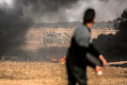April 13, 2018 - Gaza, Palestine - Palestinians gather during clashes with Israeli security forces in a tent city protest where Palestinians demand the right to return to their homeland, at the Israel-Gaza border, in Khan Younis in the southern Gaza Strip, April 13, 2018. (Credit Image: © Momen Faiz/NurPhoto via ZUMA Press)