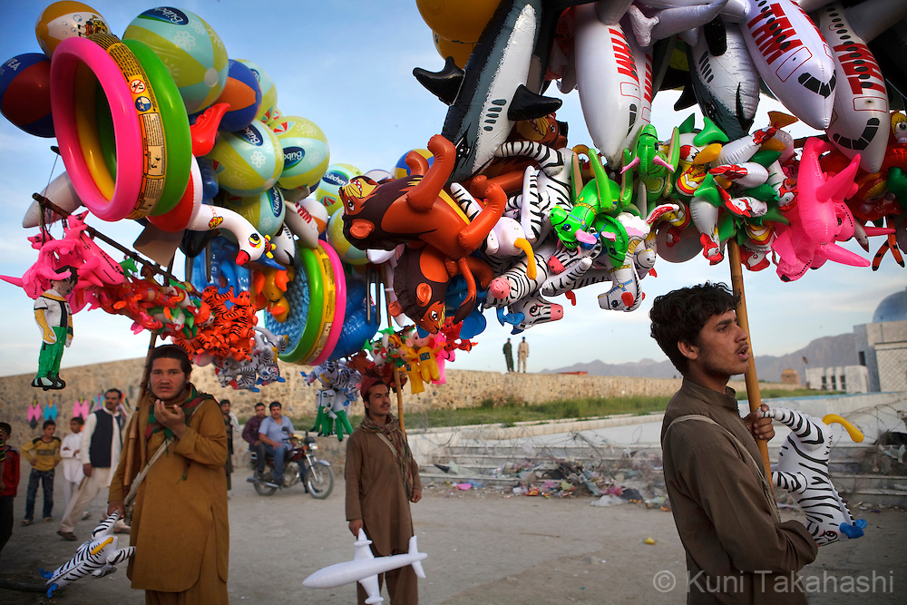 (Kabul Afghanistan - May 4, 2012).Balloon vendors walk around on top of the hill in Kabul, Afghanistan on May 4, 2012 while children fly kites. With an estimated population of 30 million, the war-torn country has been struggling to rebuild while political instability continues. .(Photo by Kuni Takahashi)