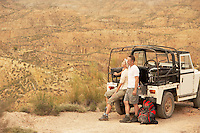 Couple sitting in back of four wheel drive car on cliff edge in desert