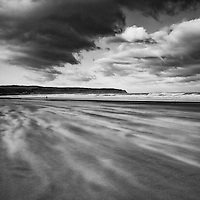 Lone figure walking along windswept beach under stormy skies at Whitby, North Yorkshire, England