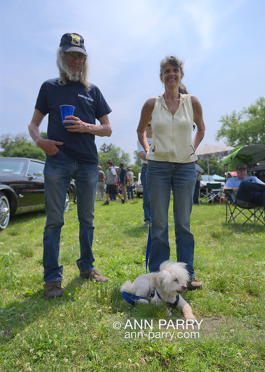 Old Westbury, New York, USA. June 2, 2019. L-R, RUSTY BECKER and DEBBIE DUGAN, both of Glen Head, and SAMMY, a 14-year-old Bichon Poo, a Bichon Poodle cross (Bichapoo), are at the 53rd Annual Spring Meet Antique Car Show. Dugan entered her 1951 Chevy pickup truck in the show. Event was sponsored by the Greater NY Region (NYGR) of the Antique Automobile Club of America (AACA), at Old Westbury Gardens, a Long Island Gold Coast estate.