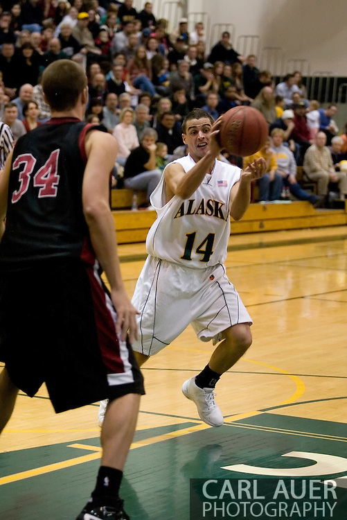1/6/2006: Junior guard Luke Cooper (14) of the UAA Seawolves dishes a no look pass through the Wildcat defense as Anchorage goes on to beat the visiting Central Washington Wildcats, 80-60 at the Wells Fargo Sports Complex on the campus of UAA.<br />