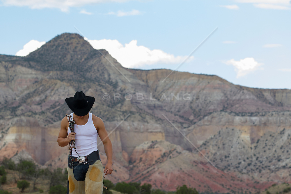 handsome young cowboy walking in the New Mexico landscape