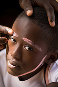 A boy's face is painted with chalk to simulated white facial hair of an elderly man for a theater production.Northern Ghana, Wednesday November 12, 2008.