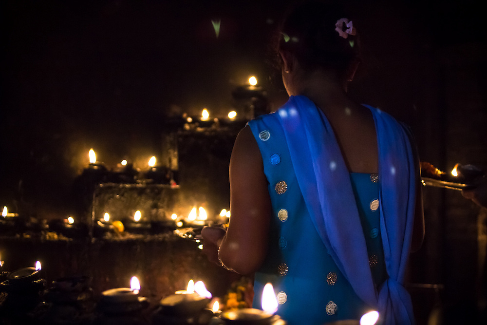 A hindu woman lights candles in a small temple during Tihar, also known as Deepawali or the Festival of Lights, in Kathmandu, Nepal.