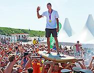 DEN BURG - Dorian van Rijsselberghe wordt op een surfplank gedragen op het strand bij Paal 17. De windsurfer, die goud won op de Olympische Spelen, werd gehuldigd op zijn eiland Texel.