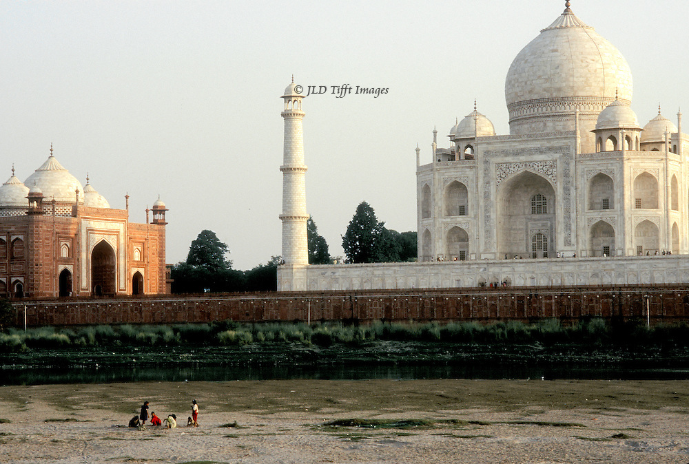 Taj Mahal at sunset from across the Jumna River.  Water is very low,  Six or seven people are gathering buffalo pats in the sand, with the Taj and its guest house just beyond.