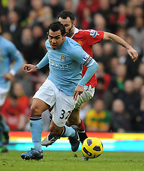 Carlos Tevez Glides Past Ryan Giggs during the Barclays Premier League match between Manchester United and Manchester City at Old Trafford on February 12, 2011 in Manchester, England.
