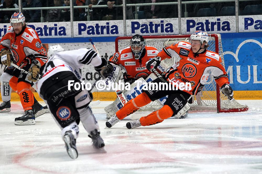 22.04.2010, Patria Areena, H?meenlinna..J??kiekon SM-liiga 2009-10, playoffs 1. loppuottelu HPK - TPS..Jens SkOElberg laukoo kiekon ohi HPK:n Teemu Lassilan ja TPS siirtyy 2-1 johtoon, Joonas Kemppainen ei pysty peitt?m??n.©Juha Tamminen.