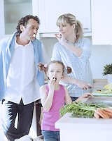 Family making a healthy salad in the kitchen