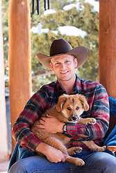 cowboy holding a puppy in his lap