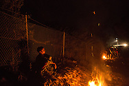 A boy watches sparks rise from a fire on the night of October 19, 2015 while waiting in line with his family at the Moria registration camp on the island of Lesvos, Greece. Asylum seekers who arrived on Lesvos by sea from Turkey are required to be registered and approved to travel by Greek police before leaving the island. In October and November, over 300,000 thousand asylum seekers were registered at Moria and other hotspots on Lesvos in 2015. Most waited for up to a week, sleeping on the group with limited access to food, water and no bathrooms, in a line that stretched for over a kilometer to be registered at Moria.