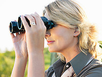 Close-up of adult woman looking through binoculars