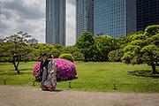 A wedding couple poses for a photo shoot at Hamarikyu Gardens