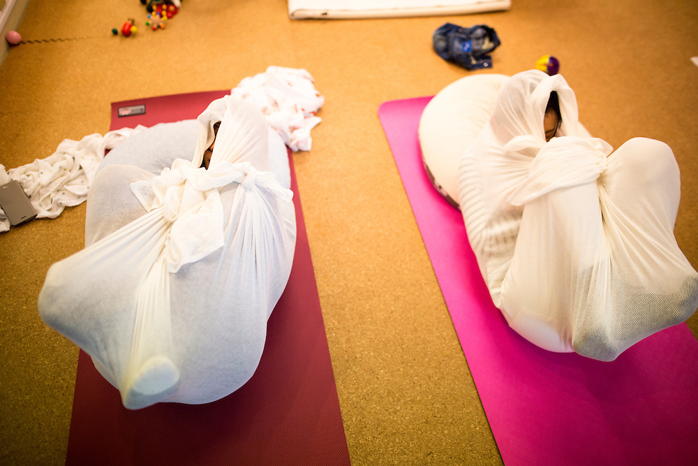 """TOKYO, JAPAN - JANUARY 29 : Participants wrapped with white cloth during a workshop called """"Otonamaki"""", which directly translates to adult wrapping in Tokyo, Japan on Sunday, January 29, 2017. Otonamaki is a Japanese therapeutic method meant to alleviate posture problems and stiffness. (Photo by Richard Atrero de Guzman/ANADOLU Agency)"""