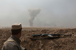 20/10/2016. Bashiqa, Iraq. A peshmerga fighter looks towards a large explosion, possibly from a coalition airstrike, during a offensive to retake the Islamic State held city of Bashiqa, Iraq, today {(date}).<br /> <br /> Launched in the early hours of today with support from coalition special forces and air strikes, the attack is part of the larger operation to retake Mosul from the Islamic State, and involves both the Kurds and the Iraqi Army. The city of Bashiqa, around 9 miles north of Mosul, is one of several gateway areas that must be taken before any attempted offensive on Mosul itself.<br /> <br /> Despite the peshmerga suffering several casualties after militants fought back using mortars, heavy machine guns and snipers, the Kurdish forces were quickly taking ground with Haider al-Abadi, the Iraqi prime minister, stating that the operation to retake Mosul was progressing faster than expected. Photo credit: Matt Cetti-Roberts/LNP