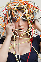 Shocked young woman's head tangled in colorful cables over gray background