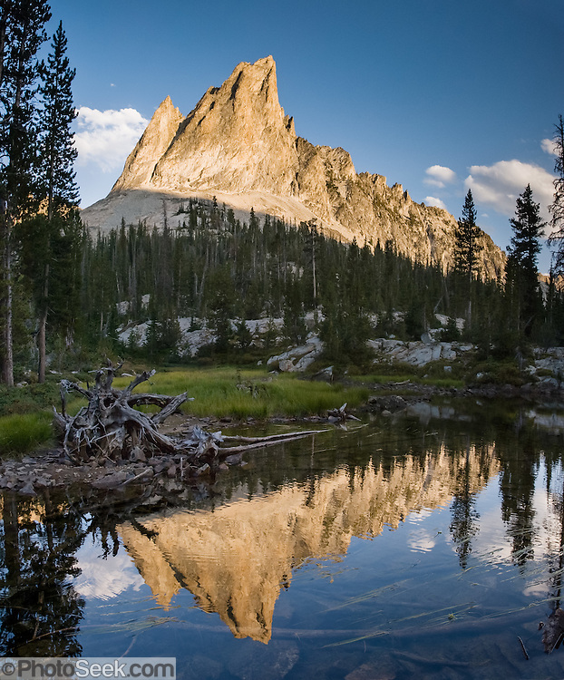The pyramidal peak of El Capitan (9846 feet or 3001 elevation) reflects in the outlet stream of Alice Lake (Pettit Lake Creek) in Sawtooth Wilderness, Blaine County, Idaho, USA. The Sawtooth Range (part of the Rocky Mountains) are made of pink granite of the 50 million year old Sawtooth batholith. Sawtooth Wilderness, managed by the US Forest Service within Sawtooth National Recreation Area, has some of the best air quality in the lower 48 states (says the US EPA). Panorama stitched from 3 overlapping photos.