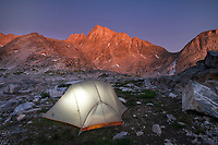 Alpenglow over backcountry camp with illuminated tent in Indian Basin, Harrower Peak is in the distance, Bridger Wilderness,  Wind River Range Wyoming