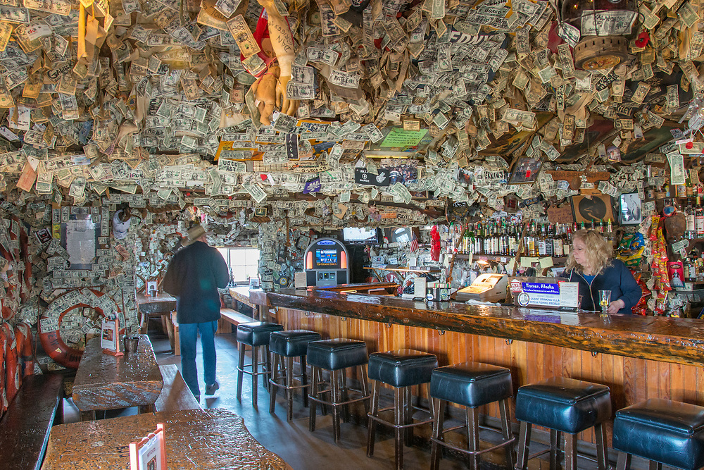 At the end of the road on the Kenai Peninsula, in Homer,Ak.,is the famous Salty Dog Bar. Originally a lighthouse warning boaters, it is a bar famous for its uniquely covered interior plastered with paper money, signed by the gifter.