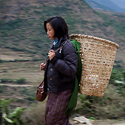 A farmer girl walking on the road with a straw basket near Trongsa, Bhutan, Asia