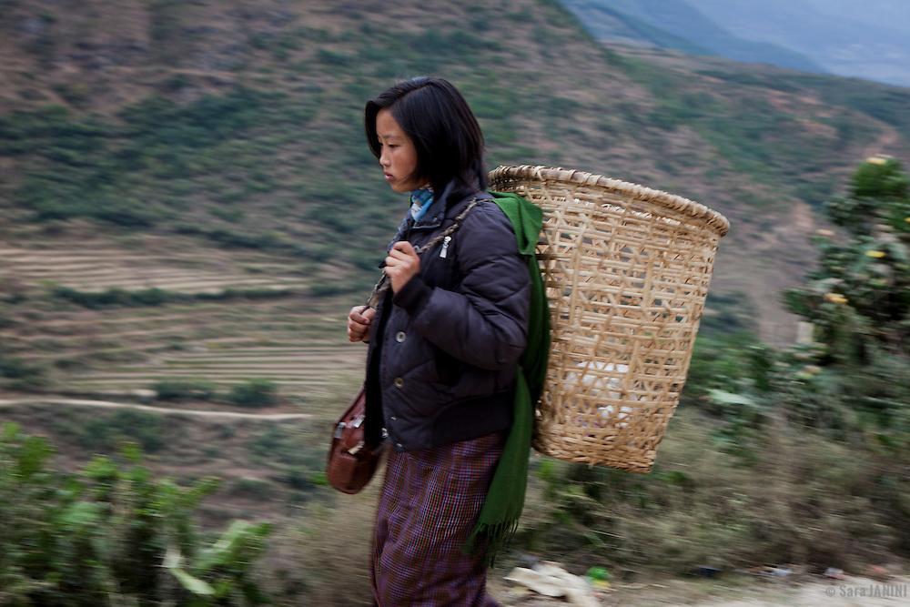 A farmer girl walking on the road with a straw basket near Trongsa, Bhutan, Asia