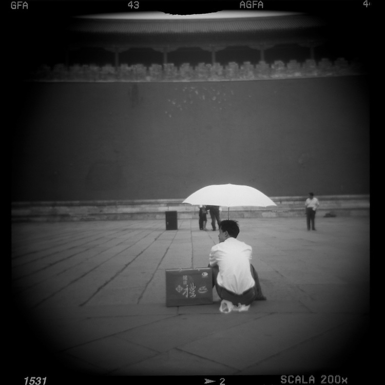 Asia, China, Beijing, Blurred black and white image of man sitting under umbrella near Gate of Heavenly Peace in the Forbidden City on summer afternoon