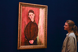 "© Licensed to London News Pictures. 14/06/2019. LONDON, UK. A staff member views ""Jeune Homme Assis, Les Mains Croisées sure les Genoux"", 1918, by Amedeo Modigliani (Est. £16-24m). Preview of Impressionist and Modern art sales, which will take place at Sotheby's New Bond Street on 18 and 19 June 2019. Photo credit: Stephen Chung/LNP"