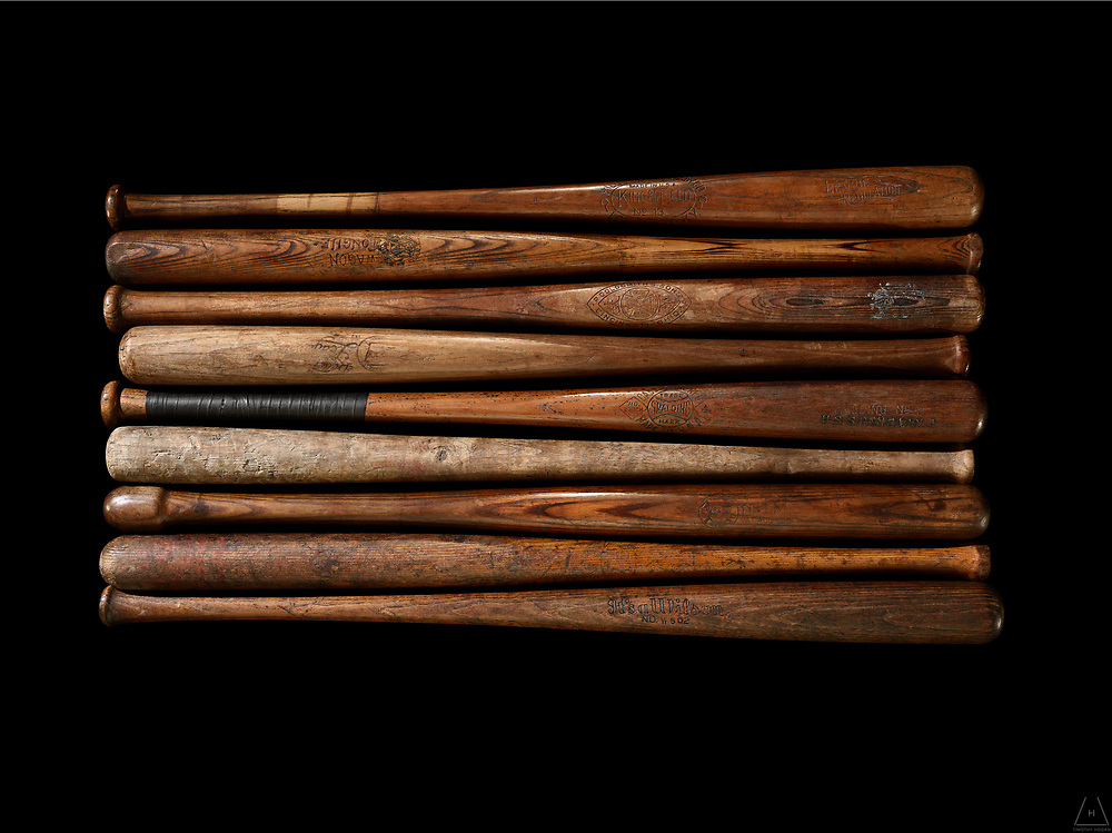 A group shot of antique baseball bats in alternating order with exquisite wood grain detailing and subtle highlights