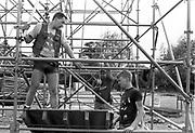 Member of scaffolding crew pulling on rope, Glastonbury, Somerset, 1989