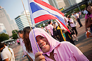 "Apr. 2, 2010 - BANGKOK, THAILAND: A Pink Shirt uses a pink towel to shield her from the sun at a peace rally in Bangkok Friday. Thousands of ""Pink Shirts,"" who claim to be neither ""Red Shirts"" nor ""Yellow Shirts"" nicknames for Thailand's dueling political forces, gathered in Lumpini Park in central Bangkok Friday evening to call for ""peace in the land,"" a play on the Red Shirts slogan, ""Red in the Land."" The ""Pink Shirts"" represented educators, business people and people in the tourist industry, all of which have been hurt by the ongoing political protests that have disrupted life in the Thai capital. The ""Pink Shirts"" stressed their loyalty to His Majesty Bhumibol Adulyadej, the King of Thailand, and chanted for the Red Shirts to ""Get Out!"" of Bangkok.    PHOTO BY JACK KURTZ"