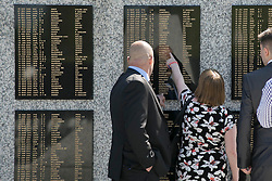 © Licensed to London News Pictures. 11/06/2015. National Memorial Arboretum, Alrewas, Staffordshire, UK. The service to mark the Rededication of the Bastion Memorial. The memorial was begun in Helmand Province in 2006, deconstructed in 2014 and now replicated at the National Memorial Arboretum in Staffordshire. Around two thousand people took part in the service including HRH Prince Harry, the Prime Minister David Cameron and senior members of the Armed Forces. Pictured a family in front of the wall. Photo credit : Dave Warren/LNP