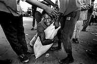 A man cries as he tries to hold onto a bag of sugar he looted from a warehouse as others try to take it from him.