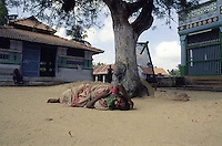 TAMIL NADU, MARCH 1994.A woman lying on the ground is wailing and rolling over in a state of distress.