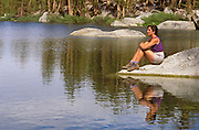 Woman sitting on rock on the shore of Gilbert Lake, John Muir Wilderness, Inyo National Forest, Sierra Nevada Mountains, California