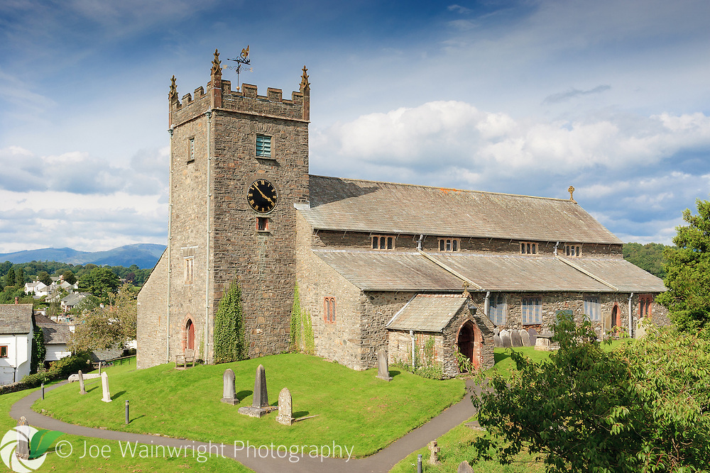 St Michael and All Angels Church, Hawkshead, Cumbria, with the Lake District Hills in the background, photographed on a sunny August afternoon.