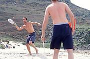 Two men playing beach tennis, shirts off, Cornwall, UK 2004