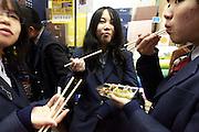 Japanese school girls eating in the street during Torino no Ichi