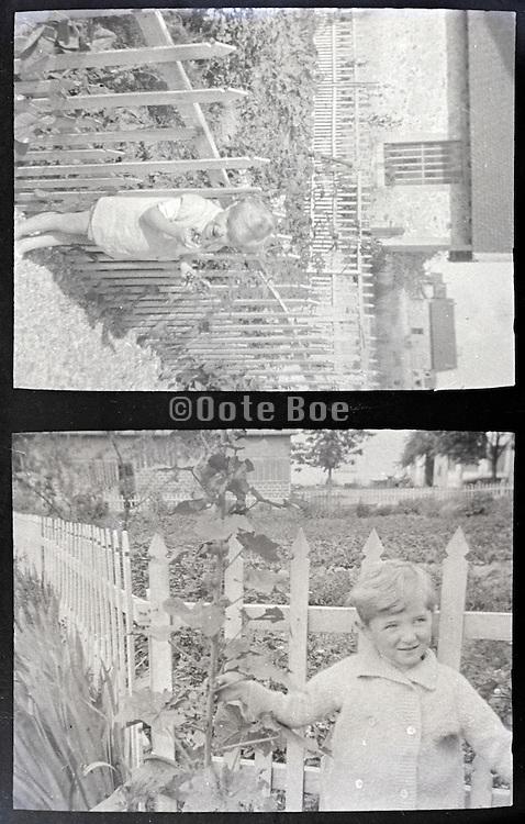 little child by garden fence 1900s