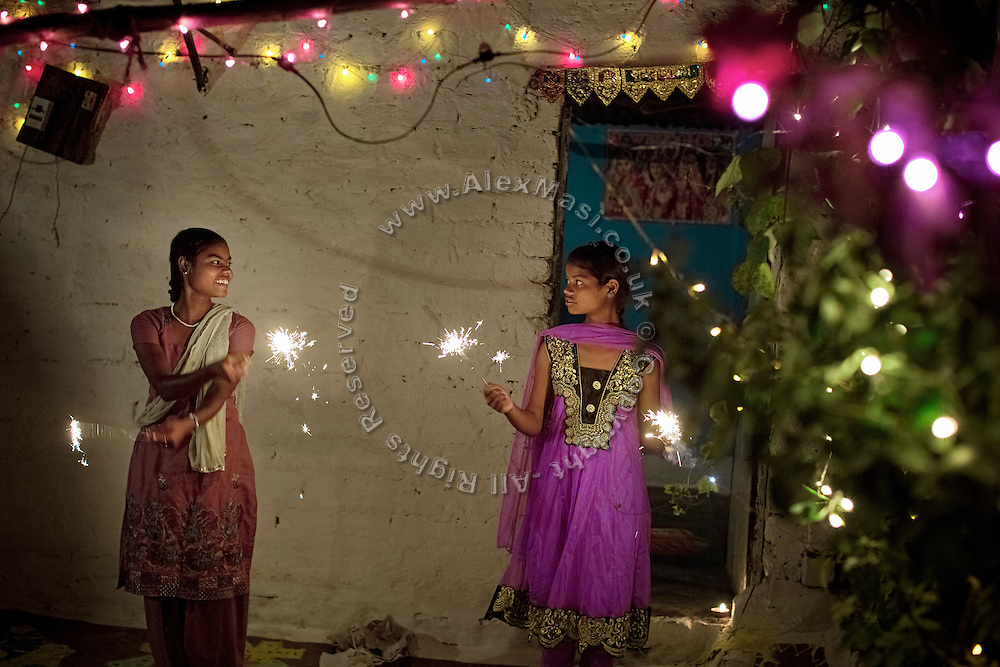 Poonam, 12, (right) is celebrating Diwali, the Hindu festival of lights, next to her oldest sister Arti, 18, in the front yard of their family's newly built home in Oriya Basti, one of the water-contaminated colonies in Bhopal, central India, near the abandoned Union Carbide (now DOW Chemical) industrial complex, site of the infamous '1984 Gas Disaster'.