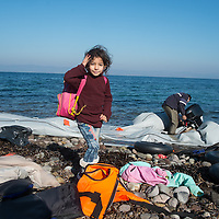 GREECE, Lesbos, October 2015: Immediately after arrival at the shore, the rubber dinghies are cut into pieces and the engine is being taken away. Rumors are that the engines are being sold back to the smugglers in Turkey. This child has just collected her belongings from the beach.<br />