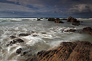The incoming tide washes over rocks on the beach at Duckpool in northern Cornwall, near Bude