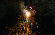 A welder joins wire cages with an oxy-acetylene torch for precast concrete pipework at Hanson construction factory, Dallas.