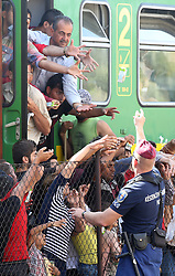 © London News Pictures. 04/09/2015. Police hand out provisions to migrants at Bicske train station in Hungary as a tense stand-off between police and migrants  continues into a second day. On Thursday, police let the migrants board the train in Budapest but then tried to force them off at a refugee camp to the west of the capital.  Picture by Paul Hackett/LNP