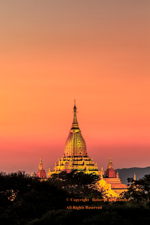 The Buddhist Ananda Temple golden shine is complimented when set against this peach-golden sky, Bagan Myanmar.
