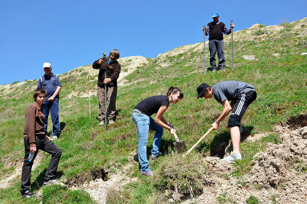 Planting of trees by school students under mountain Olympus. Sparmos village, Thessaly region, central Greece.