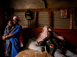 "Michael Sithole (b.1952) in his bedroom  with his wife Mabidiso and their son Khapathe.  Sithole was an MK commander and went into exile in 1976. He did not return to South Africa until 1993, spending the interim training and fighting abroad.  ""I want to live a life that normal people live. I didn't have that because I went into exile. Now I am stuck.  There is nothing happening."""