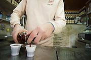 "The barman at ""Ginjinha"" in Lisbon serving a shot of cherry liquor (ginjinha)"