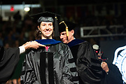 Catherine Early is hooded by her Ph. D. adviser Dr. Larry Witmer at graduate commencement. Photo by Ben Siegel