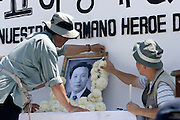 14 SEPTEMBER 2003 - CANCUN, QUINTANA ROO, MEXICO:  Korean men put flowers around a photo of Lee Kyung-hae Sunday at a shrine dedicated to the Korean farm activists who publicly committed suicide Wednesday in Cancun to protest World Trade Organization agricultural policies, has been built where he died in a park in Cancun. Thousands of protestors opposed to the World Trade Organization and globalization have come to Cancun to protest the WTO meetings taking place in the hotel zone. Mexican police restricted most of the anti-globalization protestors to downtown Cancun, about five miles from the convention center.  PHOTO BY JACK KURTZ